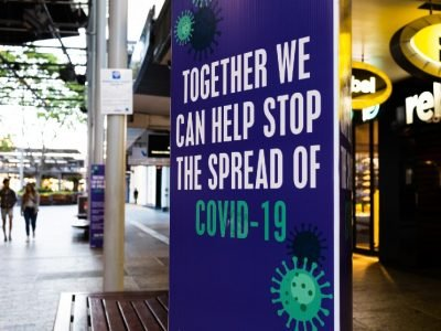 An outdoor shopping area with a prominent blue sign that says together we can stop the spread of COVID