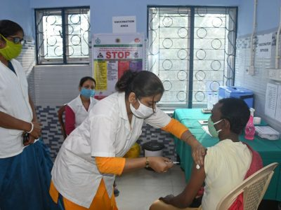 Photo of a woman getting vaccinated with 3 nurses