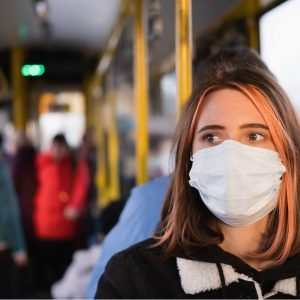 Photo showing a woman wearing a mask sitting on a bus